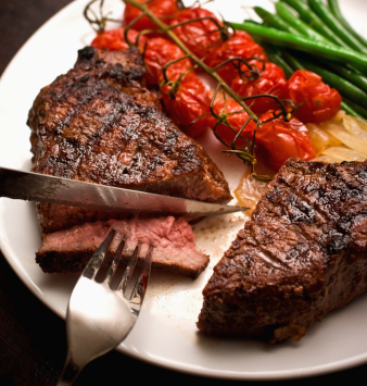 Striploin steak being cut with knife and fork. Other variations available.